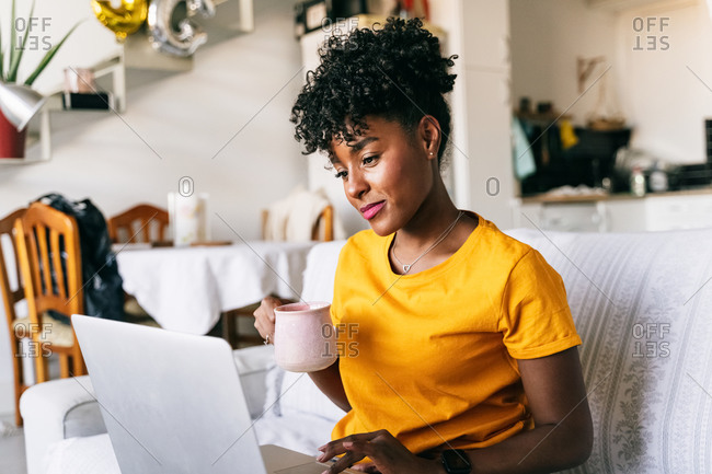 Focused young African American female freelancer with cup of coffee in hand sitting on sofa and browsing laptop while working remotely on project at home