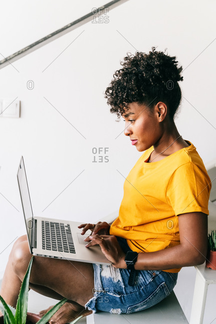 Focused young African American female freelancer sitting and browsing laptop while working remotely on project at home