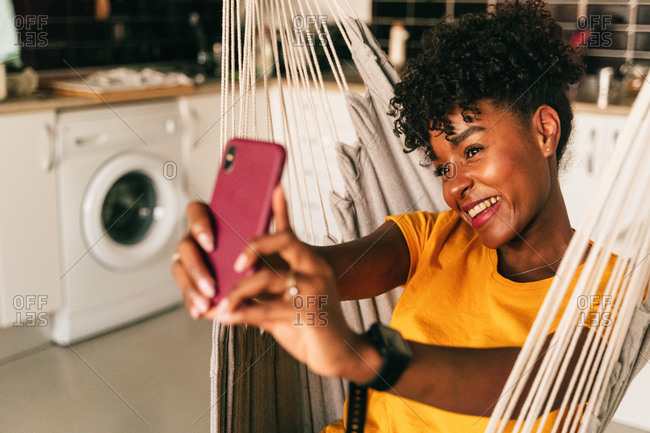 Positive African American curly haired female student in casual clothes sitting in hammock and taking selfie on mobile phone while spending free time at home