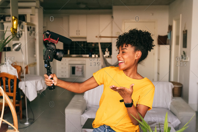 Cheerful young African American female blogger recording video while preparing content for social networks at home