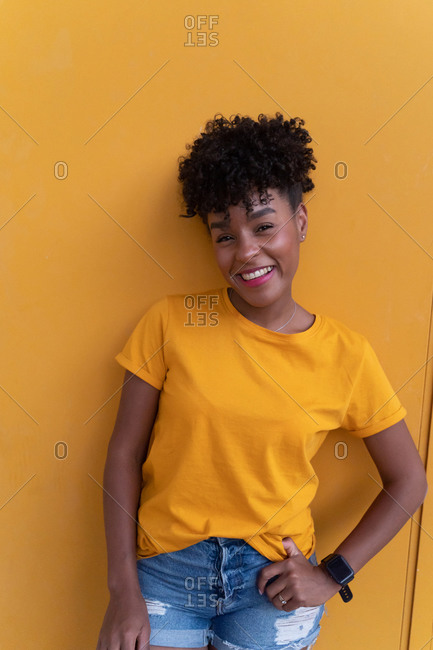 Happy young African American female with curly hair wearing bright yellow shirt and jeans standing against yellow wall and looking at camera