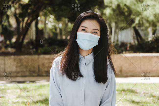 Positive young ethnic lady with dark long hair in elegant shirt and face mask relaxing in green park on sunny day and looking at camera