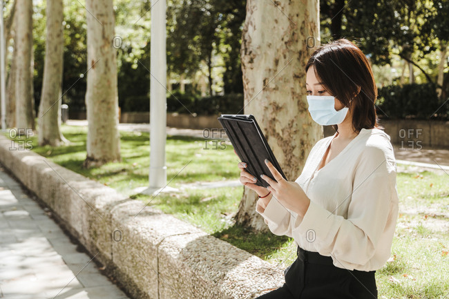 Attentive young Asian female freelancer in formal clothes and medical mask working on tablet while sitting in green park on sunny day