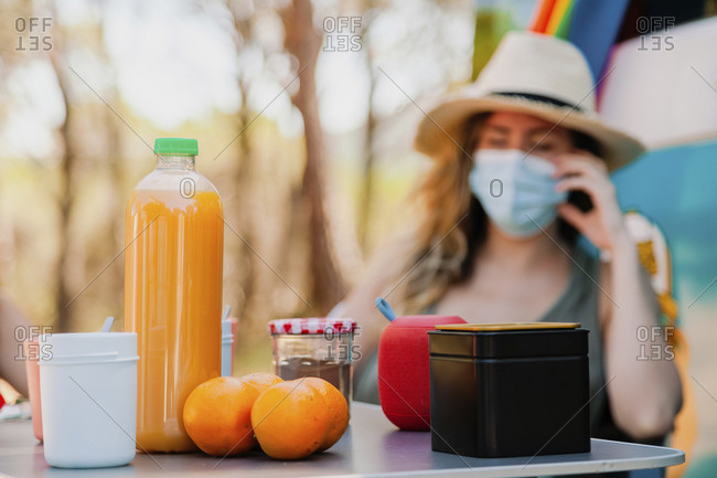 Blurred female in medical mask relaxing in woods in summer while sitting in front of picnic table with juice and fruits