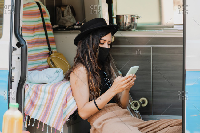 Traveling female wearing protective mask sitting in van and surfing Internet on mobile phone while resting during summer holiday