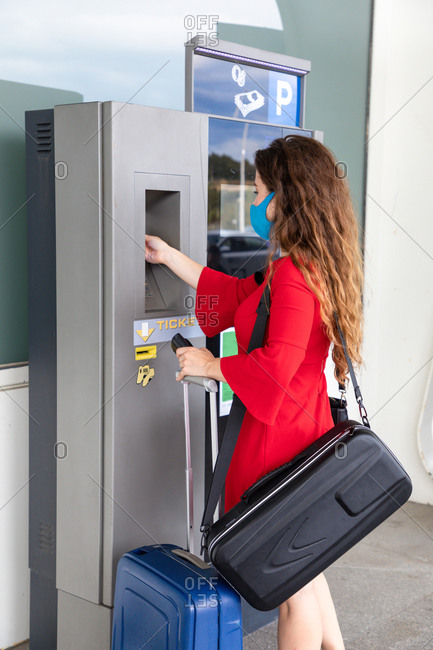 Side view of female tourist getting ticket from self service machine before flight in airport
