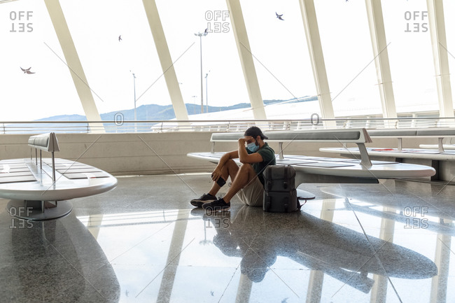 Side view of discouraged male tourist in protective mask sitting on floor in departure lounge of airport with phone while waiting for flight during coronavirus pandemic