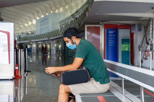 Side view of male tourist in protective mask sitting in departure lounge of airport and using mobile phone while waiting for flight during coronavirus pandemic