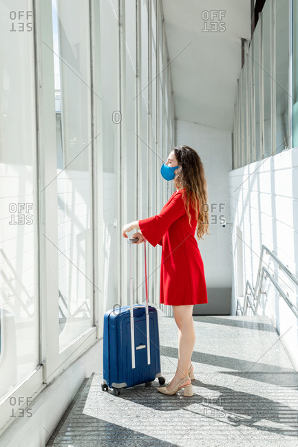 Side view of female tourist in protective mask standing with suitcase in airport and waiting for flight while looking out of window