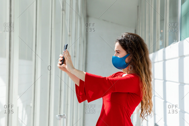 Young woman tourist wearing protective mask standing with suitcase in departure lounge in airport and taking picture with cellphone while waiting for flight during coronavirus