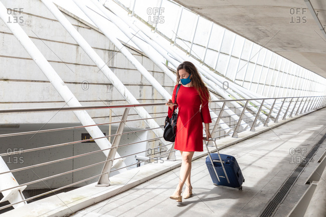 Full body of female tourist in protective mask walking with luggage along hall in airport and reading messages on smartphone while waiting for flight during coronavirus pandemic