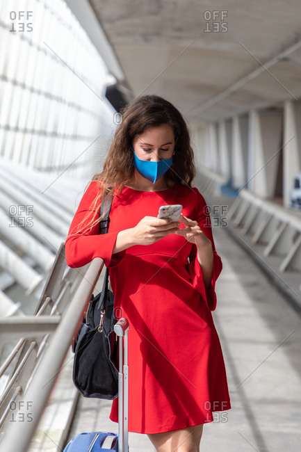 Female tourist in protective mask standing with luggage along hall in airport and reading messages on smartphone while waiting for flight during coronavirus pandemic
