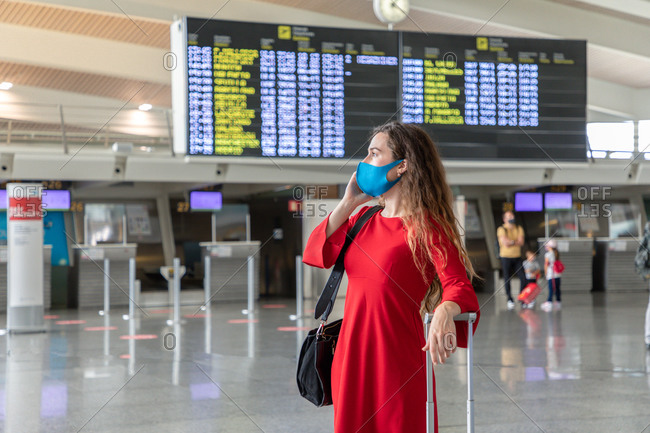 Serious female traveler in mask standing with suitcase on background of departure board and talking on the phone while waiting for flight