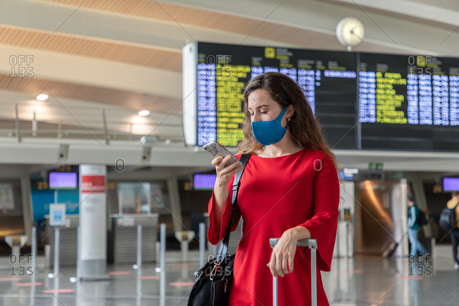 Serious female traveler in mask standing with suitcase on background of departure board and browsing cellphone while waiting for flight