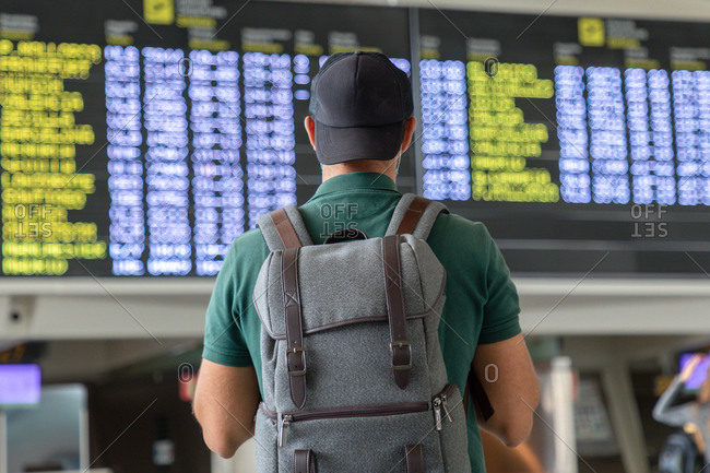 Back view of unrecognizable male traveler with backpack checking schedule on departure board while standing in international airport and waiting for flight