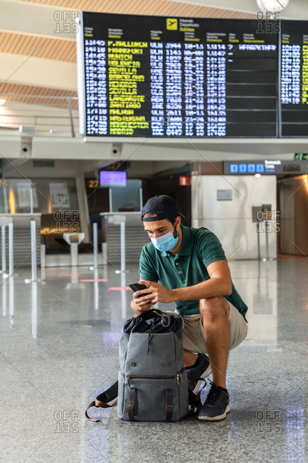 Calm male tourist squatting against departure board in airport and chatting on social media via smartphone while waiting for flight