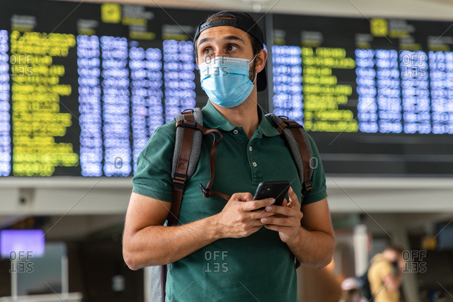 Calm male tourist standing against departure board in airport and chatting on social media via smartphone while waiting for flight