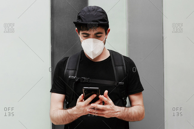 Male in black wear with rucksack using cellphone during quarantine period
