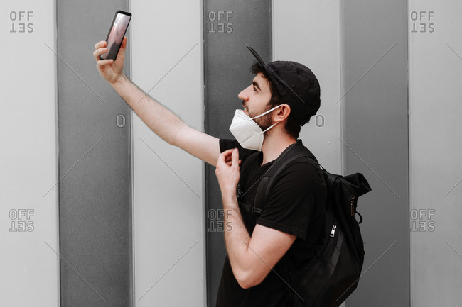 Side view of cheerful unshaven male in black wear with rucksack taking selfie on cellphone during quarantine period