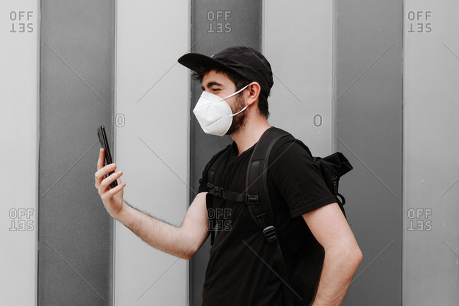 Side view of male in black wear with rucksack using cellphone during quarantine period