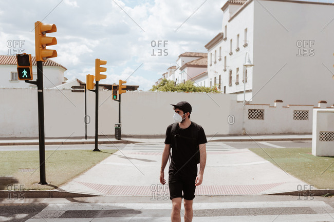 Unrecognizable guy in black outfit in respiratory mask strolling on street pavement under cloudy sky while looking away during COVID 19 pandemic