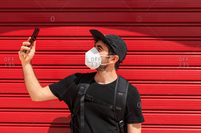 Young male in respiratory mask taking selfie on cellphone near red wall standing on the street during COVID 19 pandemic