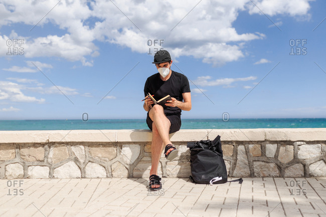 Male author in face mask and cap sitting with crossed legs on fence while taking note in diary behind ocean