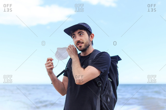 Smiling bearded male tourist in cap with backpack standing taking off protective mask standing behind ocean under blue cloudy sky