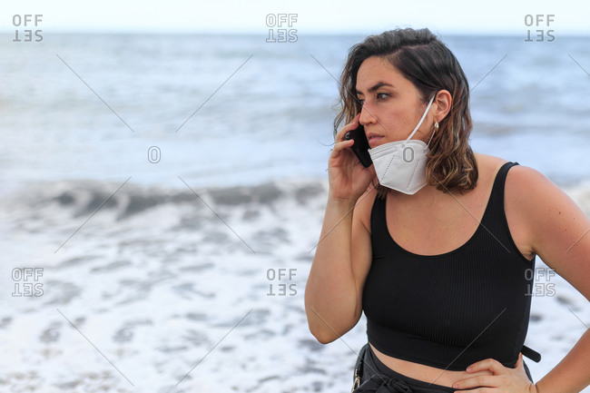 Young female tourist in mask speaking on cellphone behind foamy ocean during summer trip