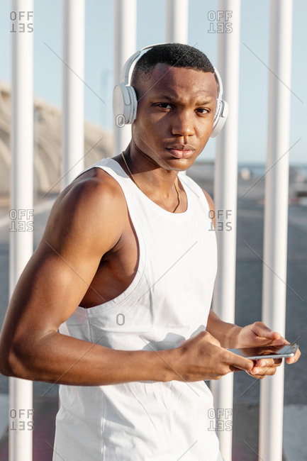 Close up of African American runner browsing mobile phone and listening to music in headphones while looking at camera training on street