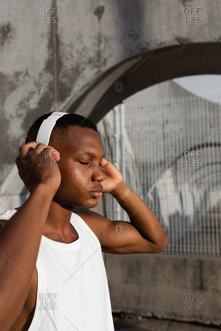 Calm African American male with eyes closed in wireless headphones listening to songs while training outdoors