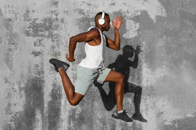 Full body side view of concentrated African American runner listening to music in headphones while jumping above ground during jogging training