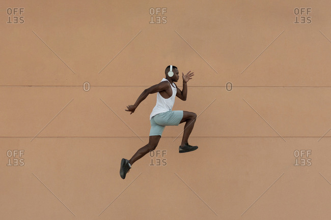 Side view full body of energetic African American sportsman in headphones jumping on air during fitness training