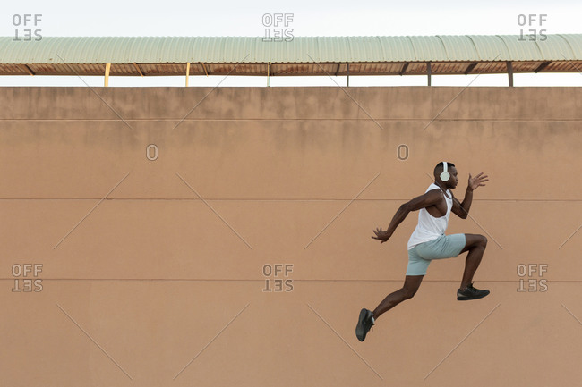 Side view full body of energetic African American sportsman in headphones jumping along pavement during fitness training