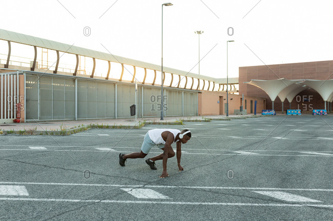 Full body side view of concentrated African American sportsman ready to run during active cardio training