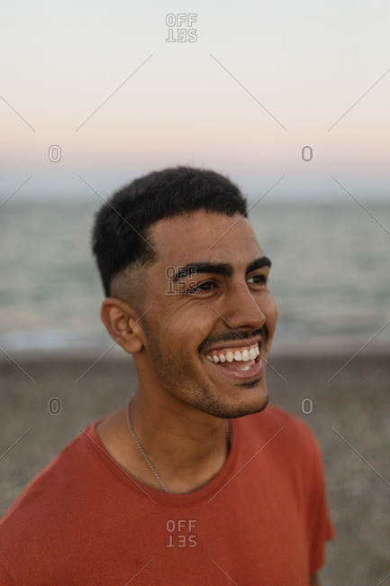 Positive ethnic male with toothy smile enjoying evening on shore of sea and looking away