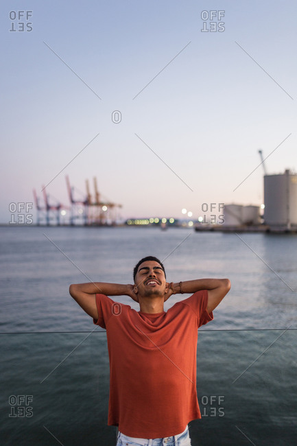 Young happy ethnic male traveler with raised arms standing behind rippled sea under sky in twilight