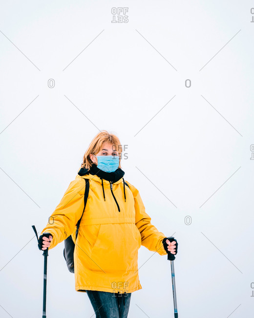 Female hiker in yellow outerwear and protective mask looking at camera while standing with trekking poles in snowy mountains