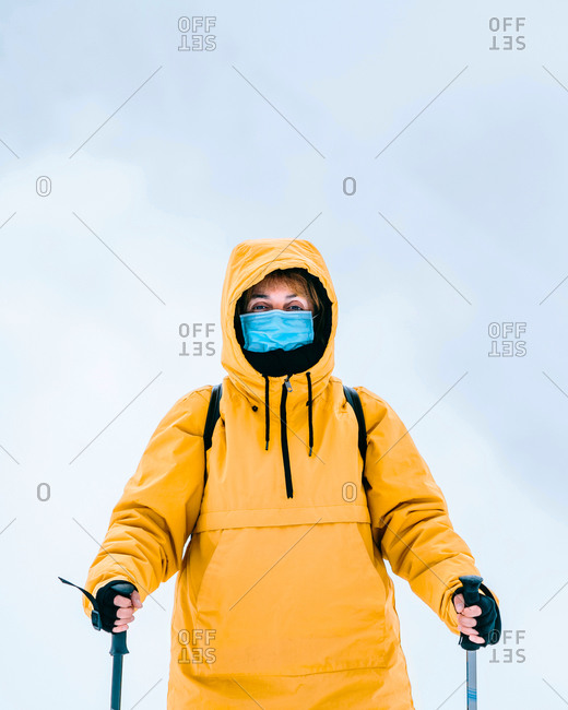 Unrecognizable female hiker in yellow outerwear and protective mask looking at camera while standing with trekking poles in snowy mountains