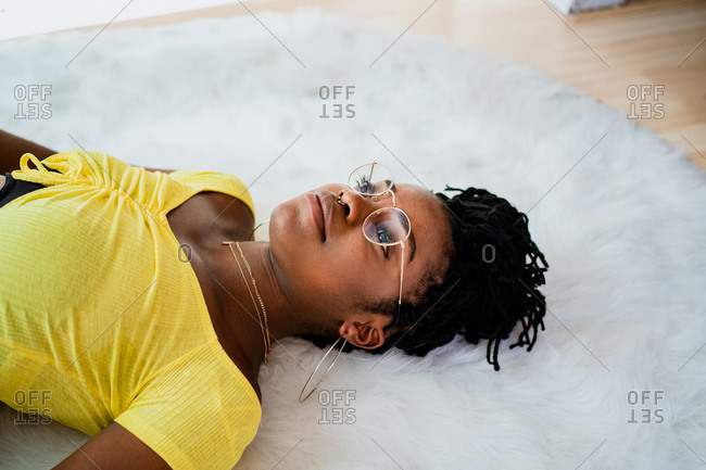 From above of African American female in casual clothes and eyeglasses lying on soft carpet while resting at home