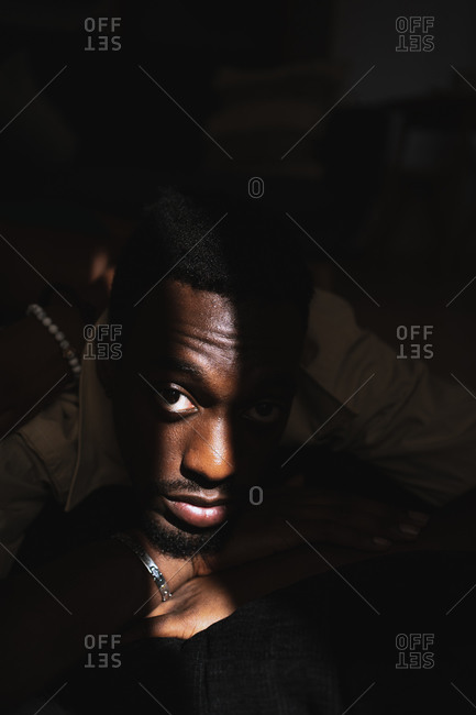 Confident young African American guy relaxing in dark room near window with sunlight on face and looking at camera