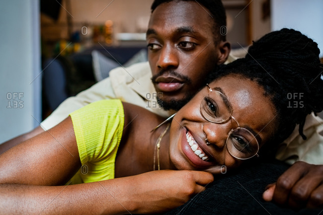 Happy young black man in casual clothes lying on back of girlfriend while spending weekend together at home
