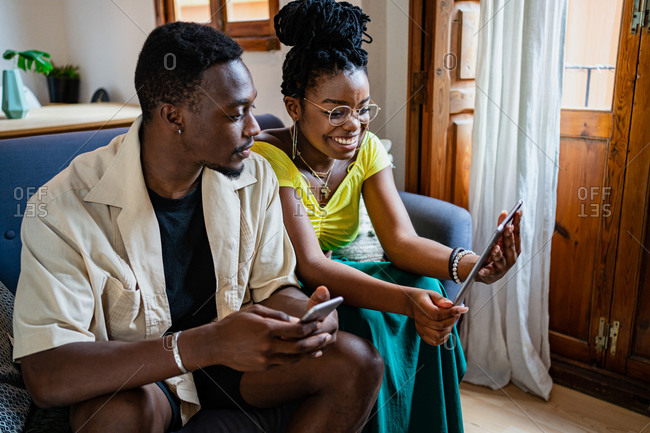 Content young African American lady reading information on tablet while resting on sofa with boyfriend using smartphone at home