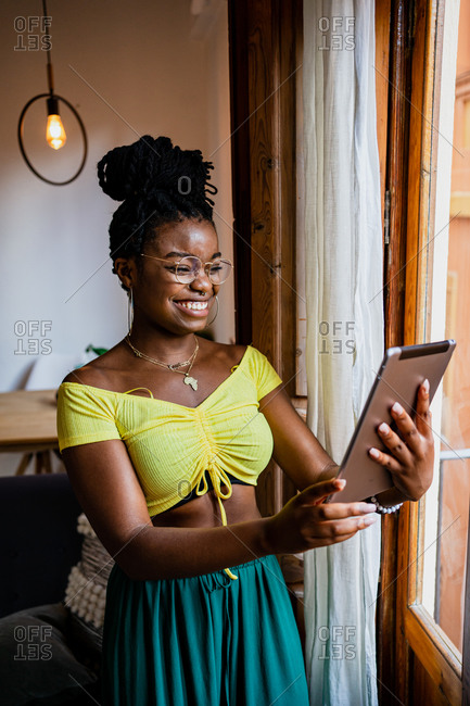 Happy young ethnic lady in stylish crop top and eyeglasses smiling while browsing tablet during remote work at home