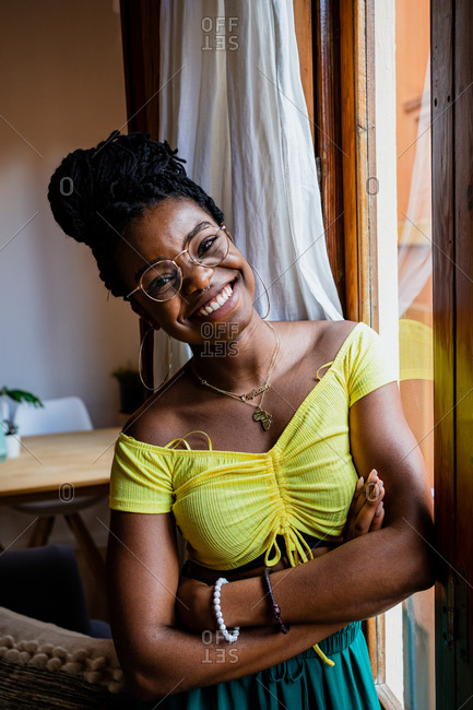 Cheerful young black female with Afro hairstyle in trendy outfit and eyeglasses standing near window at home with folded arms and looking at camera
