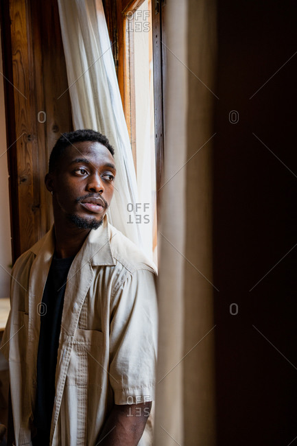 Pensive young African American guy in casual clothes looking out window while resting at home in daylight