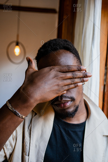 Young African American male with black short hair and beard covering face with palm in cozy bright room with lamp and drapes