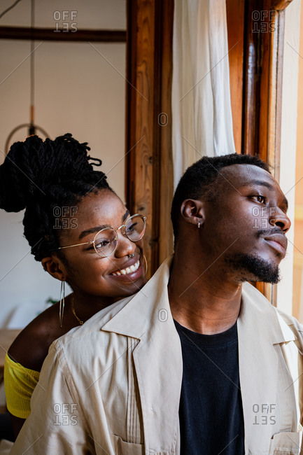 Cheerful young African American female in transparent eyeglasses with bunch looking at thoughtful man standing near window