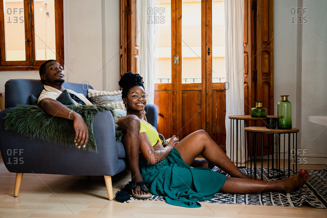 Full body side view of cheerful African American wife and husband looking at camera while resting in cozy living room with framed window and balcony