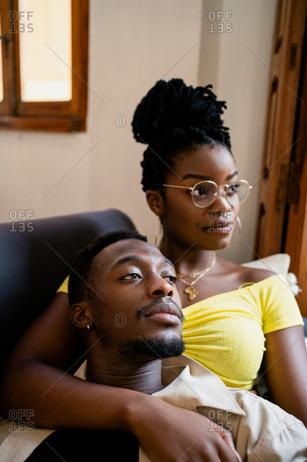 From above of cheerful African American wife looking at positive husband resting on shoulder and looking away in bright studio apartment